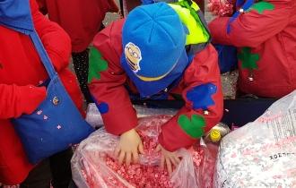 Der Leiterwagen voller Konfetti. Die Kinder stopfen sich die Taschen voll.